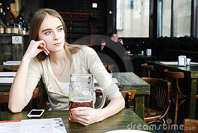 Woman with mug of alcohol beer at the cafe