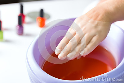 Woman in nail salon having paraffin bath