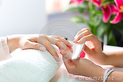 Woman in nail salon receiving manicure