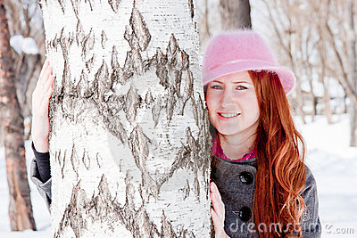 Woman near a birch in winter in a park