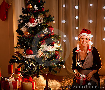 Woman near Christmas tree holding gift