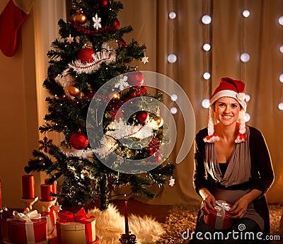 Woman near Christmas tree holding gift