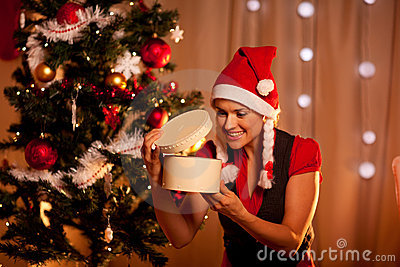 Woman near Christmas tree looking inside gift