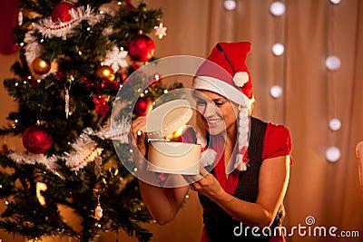 Woman near Christmas tree looking inside gift