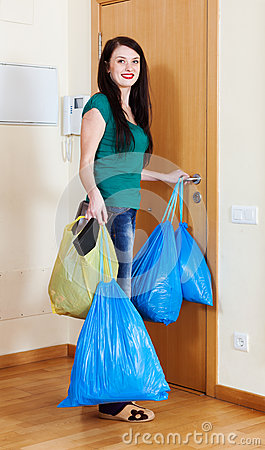 Woman near door with garbage bags