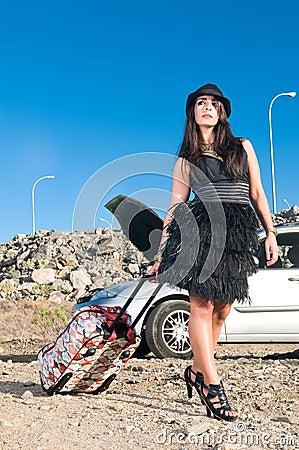 Woman near her broken car with bag