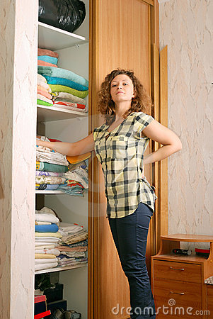Woman near wardrobe with bed linen