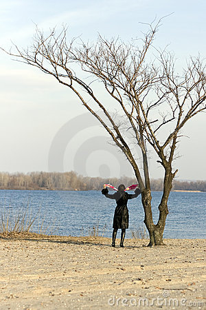 Woman next to a lone tree.