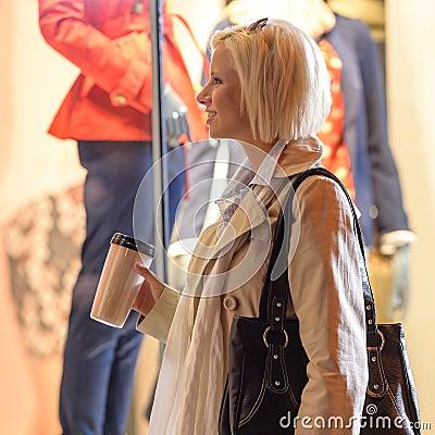 Woman night city shopping window drink coffee