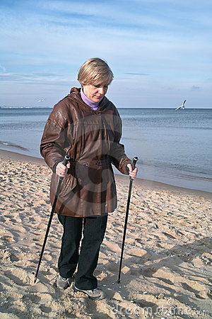 Woman Nordic walking on beach