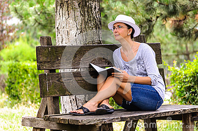 Woman with notebook on bench in park