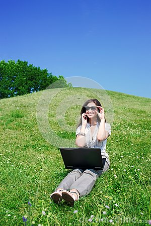 Woman with notebook and  phone sit on hill