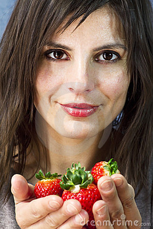woman offers strawberries on her hands