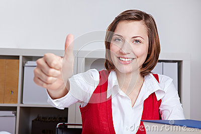 Woman in office holding thumbs up