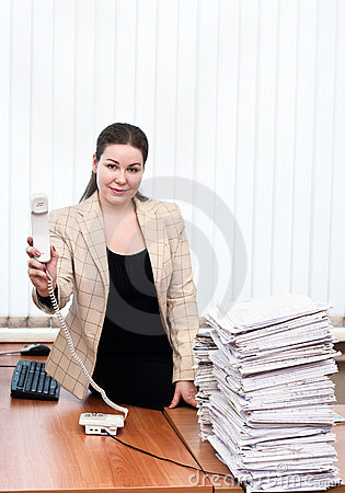 Woman in office interior holding telephone