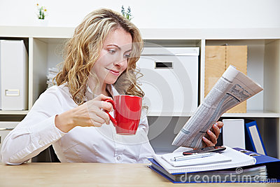 Woman in office reading newspaper