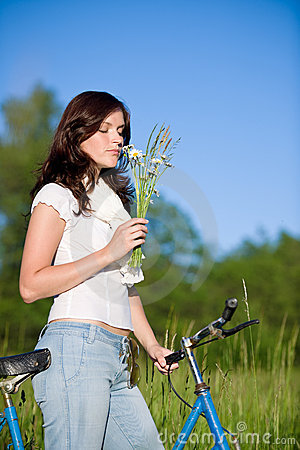 Woman with old-fashioned bike and summer flower