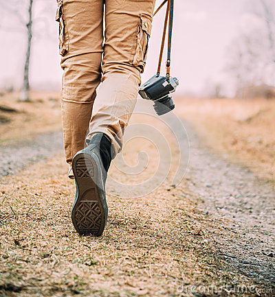 Woman with old photo camera walks on a road
