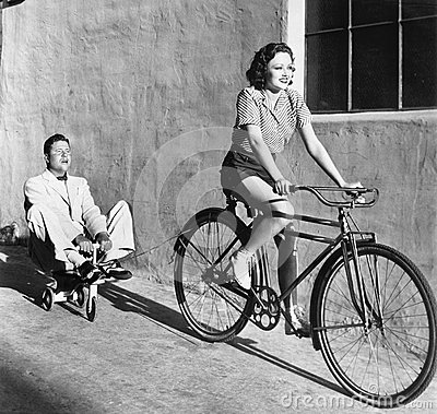 Free Woman On A Bicycle Pulling A Grown Man On A Toy Tricycle Stock Image - 52029231
