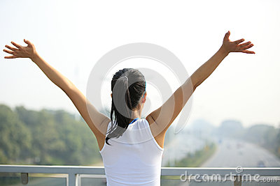 Woman open arms to the rush driveway modern city
