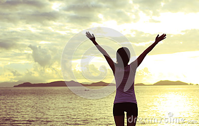 Woman open arms to sunrise
