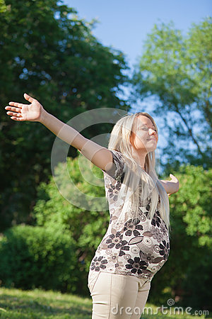 Woman with open hands enjoy sun in park