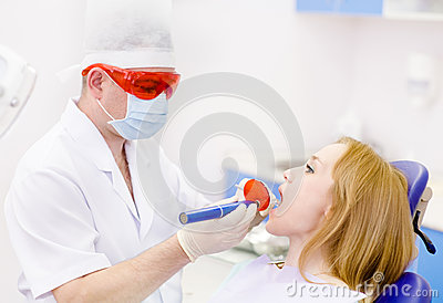 Woman with open mouth receiving dental filling drying proc