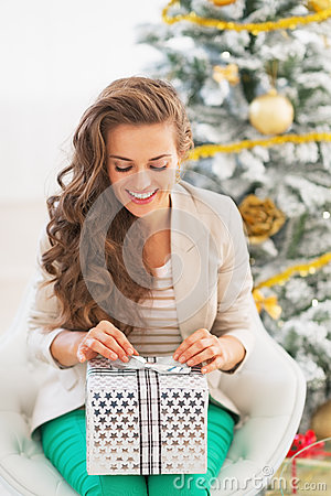 Woman Opening Christmas Present Box In Front Of Christmas ...