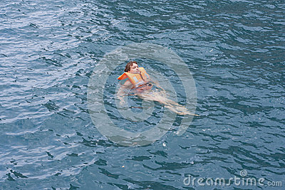 Woman in orange life jacket in water of a sea