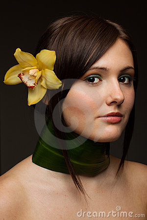 Woman with orchid and necklaces from leaf