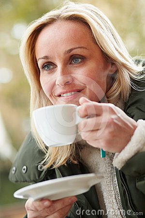 Woman In Outdoor Cafe With Hot Drink