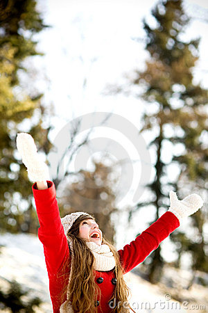 Woman outdoors with arms raised