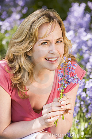 Woman outdoors holding flowers smiling