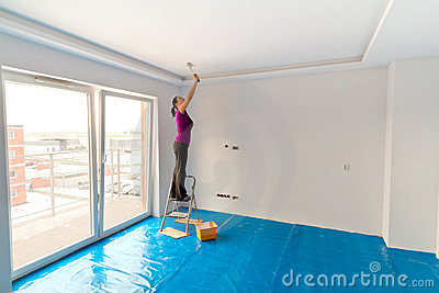 Woman painting apartment ceiling