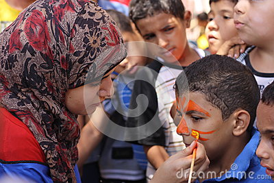 A woman painting a boys face at charity event Editorial Photography