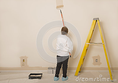 Woman Painting A Wall / Copy Space To The Left