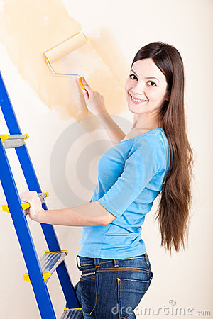 A woman is painting walls