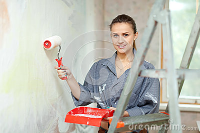 Woman paints wall  at home