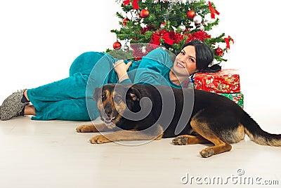 Woman in pajama and dog near Xmas tress