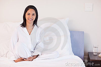 Woman in pajamas sitting on her bed