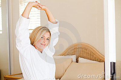 Woman in pajamas stretching