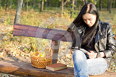 Woman on park bench using a tablet