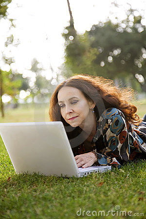 Woman in park with laptop
