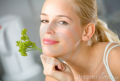 Woman with parsley at kitchen