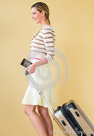 Woman With Passport And Suitcase Walking Against Colored Backgro