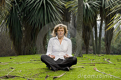 Woman peacefully meditating outside