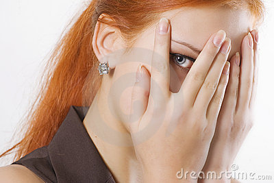 Woman peeking through fingers