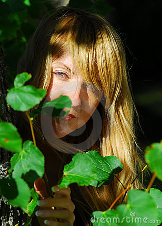 Woman peeking through leaves