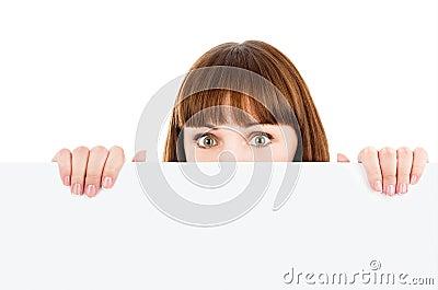 Woman peeking over blank billboard