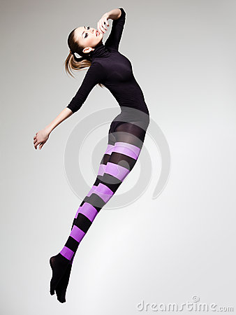Woman with perfect body jumping dressed in purple striped tights and black top